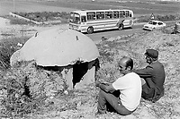 Albania. Province of Durres. Village of Arapaj. Two farmers seat in a field, watch the road and the vehicles on their way to Durres. Enver Hoxha (1908-1985) was for 40 years a dictator and a communist leader. He decided after the historic break with Russia in 1961 to protect his country from any invaders by investing in a massive fortification (more than a million bunkers were built over the years till 1985). © 2003 Didier Ruef