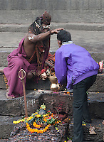 Pashupatinath, Nepal.  Sadhu (Holy Man) at Nepal's Holiest Hindu Temple Blessing a Worshiper.