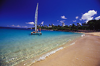 Group of people sailing a catamaran in clear blue waters off white sand beach of Waimea Bay, North Shore of Oahu, Hawaii