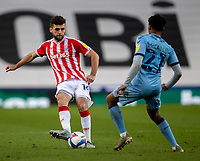 21st April 2021; Bet365 Stadium, Stoke, Staffordshire, England; English Football League Championship Football, Stoke City versus Coventry; Tommy Smith of Stoke City passes under pressure from Sam McCallum of Coventry City