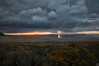 Clouds, like airborn sculptures hover over the Great Salt Lake, Utah, at sunset, when the sun suddenly bursts through.