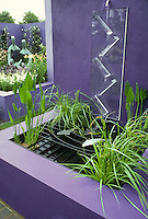 Water garden Bold purple color theme, with grating covered to protect kids & pets, modern design of raised garden beds, statues, lush flowers in raised beds, walled garden, bit of sky, waterfall feature,