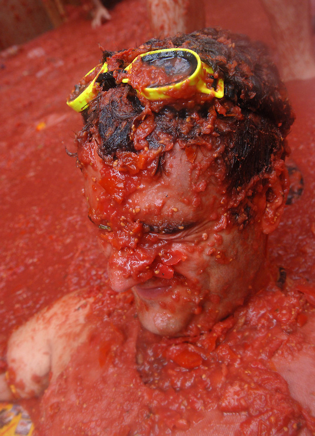 BUNYOL, SPAIN - AUGUST 31: A person with his face full of tomato in the Tomatina August 31, 2005 in Bunyol, Valencia, Spain. Approximately 45,000 people pelted each other with a little over 100.000 kilograms of tomatoes. The tomatina is known as the world's largest tomato battle. Photo by Ander Gillenea