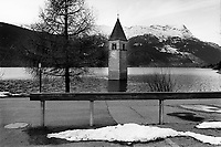 Italy. South Tyrol. Reschensee (Lago di Resia, Lake Reschen) is an artificial lake in the western portion of South Tyrol. The lake is famous for the steeple of Graun's  submerged 14th-century church. Today all that's visible above the waterline is the campanile, or bell tower, of Graun's church tower. The bells were removed from the tower on July 18, 1950, a week before the demolition of the church nave and the creation of the lake. Lake Reschen a capacity of 120 million cubic metres and its surface area of 6.6 km² makes it also the largest lake above 1,000 m in the Alps. 21.11.2017© 2017 Didier Ruef