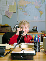 Smiling young boy sitting at a home office desk talking on the telephone. child, children,. N. Matosky, M.R. # K-9.