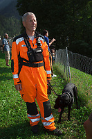 Switzerland. Canton Graubunden. Bregaglia valley. Bondo. Jeremias Janki from Redog is a rescue specialist. He wears an orange uniform, carries a radio on his chest and holds his dog on a leash. In his back, people look at a second massive landslide while the remote village is still recovering from a huge landslide caused by a giant rockslide swept down from Piz Cengalo on August 23, 2017. The man with shorts had returned to his home had to be evacuated from the village for the second time. The Swiss Association for Search and Rescue Dogs (REDOG) has created the Catastrophe Dog Unit and the Search Dog on Site Unit, which trains teams of rescue dogs and mantrailing. REDOG is a Rescue Organization of the Swiss Red Cross. As member of the Rescue Chain, REDOG is an organization recognized by the Swiss Federal Department of Development and Cooperation (DDC) and known for its operating experience in humanitarian interventions during catastrophes. 25.08.2017 © 2017 Didier Ruef