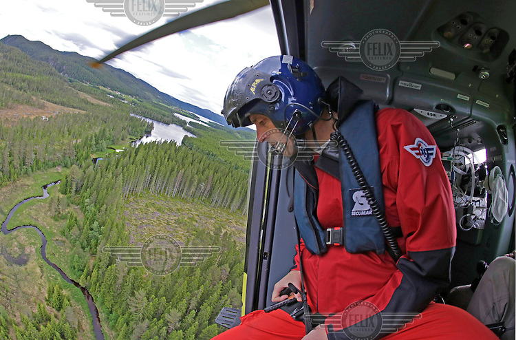 Doctor Steinar Einvik checking a field prior to landing during a training mission. Norwegian Air Ambulance operating EC 135 helicopter out of their base in Trondheim, one of eight bases operated by the company.