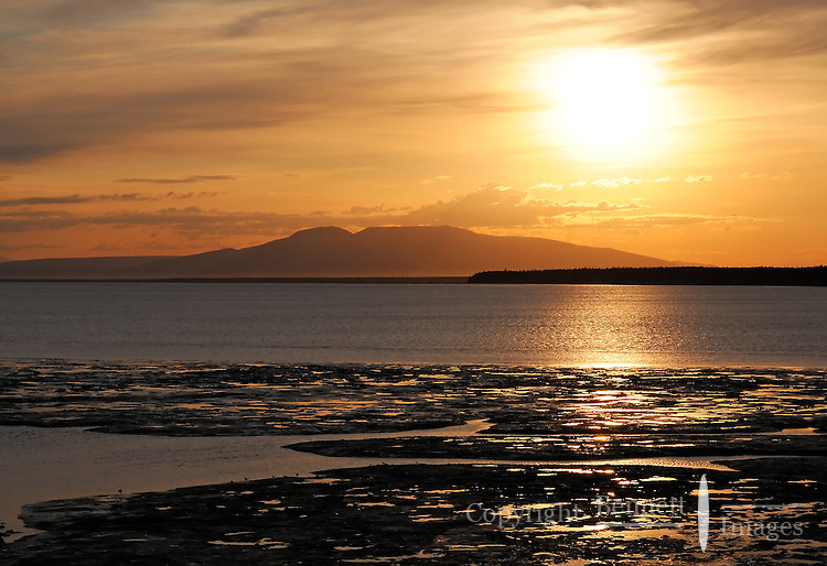 The sun sets behind Mt. Susitna, also known as Sleeping Lady, on a summer evening across Cook Inlet from Anchorage, Alaska.