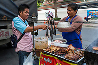 Bangkok, Thailand.  Street Food Vendor at her Stand with a Customer.