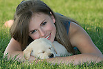 Teenager holding a sleeping Yellow Labrador retriever (AKC) puppy
