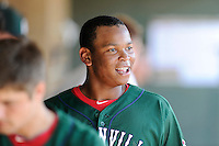 Third baseman Rafael Devers (13) of the Greenville Drive smiles in the dugout in a game against the Charleston RiverDogs on Sunday, June 28, 2015, at Fluor Field at the West End in Greenville, South Carolina. Devers is the No. 6 prospect of the Boston Red Sox, according to Baseball America. Charleston won, 12-9. (Tom Priddy/Four Seam Images)