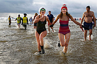 Pictured: Two women in their swimming costumes splash about in the water. Tuesday 26 December 2017<br /> Re: Hundreds took part in this year's Boxing Day Walrus Dip which see people in fancy dress taking to the sea at Cefn Sidan beach in Pembrey Country Park, west Wales, UK.