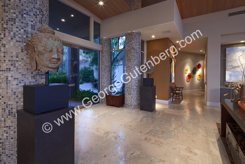 Buddha heads flank the front entry of luxury home