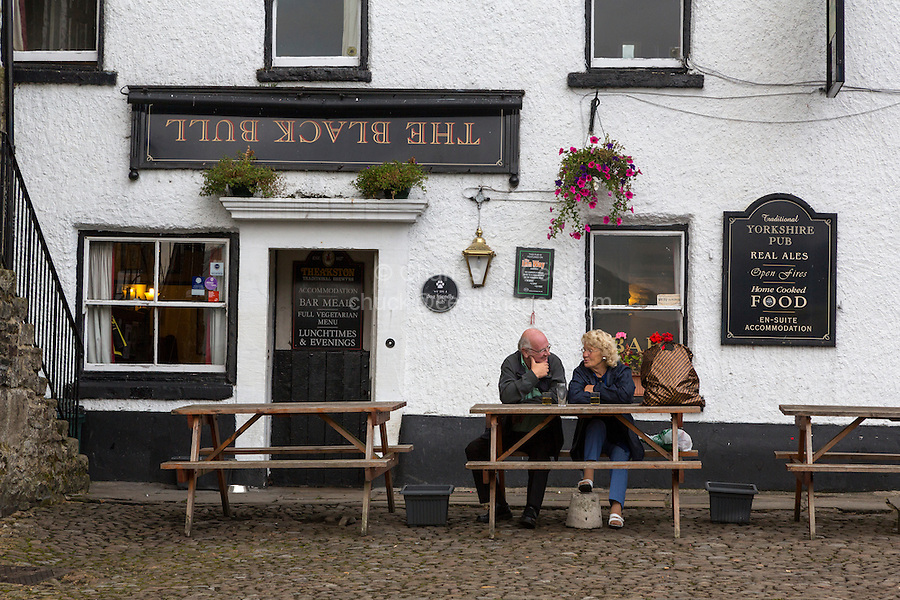 UK, England, Yorkshire, Reeth.  Couple Talking outside the Black Bull Pub.
