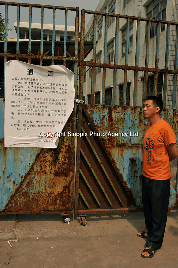 A worker stands in front of the closed factory gates belonging to Smart Union, one of several factories in Zhang Mutou in South China that went bankrupt in the current credit crisis. Smart Union, that produced toys for Mattel amongst others, left 6,000 workers jobless and penniless after they could not pay the salaries. Hundreds of factories in south China are closing due to increased labor and material costs and the current credit crissis is exasperating. The problem leaving ghost towns behind. .24 Oct 2008