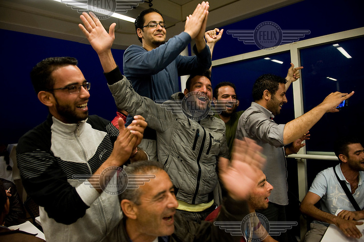 A group of Syrian refugees celebrate their rescue aboard a ferry to mainland Greece after having arrived by inflatable boat on the island of Lesbos having crossed the straits from Turkey. <br />The boat is carrying a number of refugees who landed on inflatable boats from Turkey and are being taken to mainland Greece. Every day hundreds of refugees, mainly from Syria and Afghanistan, are crossing in small overcrowded inflatable boats the six mile channel from the Turkish coast to the island of Lesbos in Greece. Many spend their life savings, over $1,000, to buy a space on these boats.