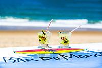 Two Caipirinha glasses with straws, on a surfboard, at the beautiful beach of Porto de Galinhas, in Pernambuco, near Recife Brazil