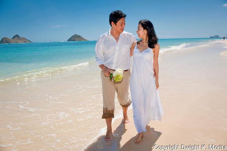Asian bride and groom stroll arm in arm on Lanikai beach as they look forward to their life as a married couple following their wedding.