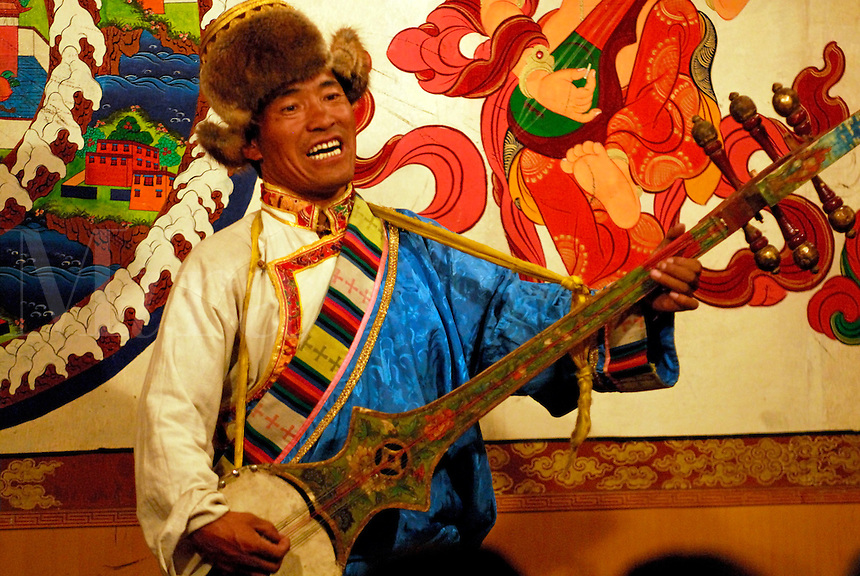 A Tibetan musician plays a traditional six-stringed lute at a Yak-Dance in Tashi II, the restaurant and internet cafe of the Kirey Hotel, Lhasa, Tibet.
