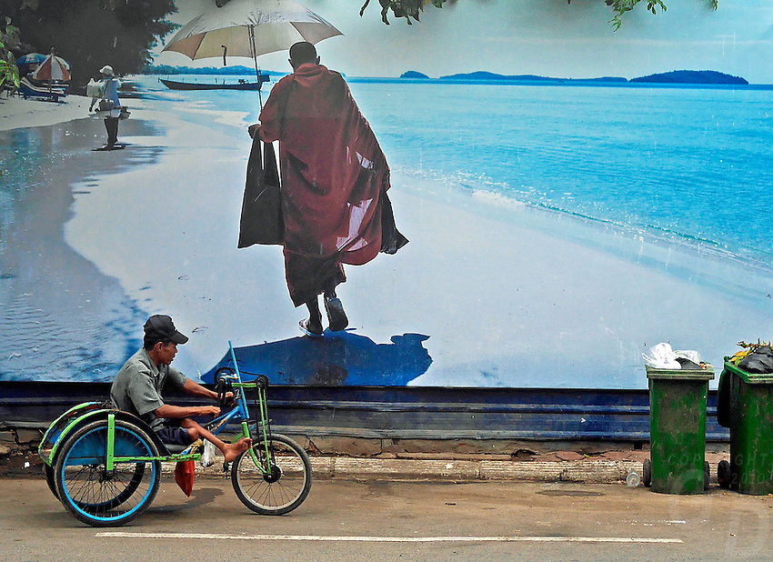 A handy cap man with his mobile transportation in front of a large street mural,street scene in Phnom Penh, Cambodia