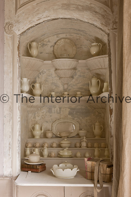 A former shrine has been transformed into a display cabinet for a collection of creamware in a corner of the sitting room