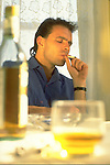 man smoking with bottle of wine on table