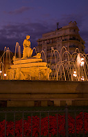 Beautiful night time exposure of fountain and flowers at  Puerta de Jerez square with excitement in Seville Spain downtown
