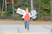 """A supporter holds signs reading """"Make America Great Again"""" and """"Cops are us / we back the blue"""" as she crosses the street after hearing Donald Trump, Jr., son of president Donald Trump and a rising Republican political star, speak at an outdoor campaign rally at The Lobster Trap in North Conway, New Hampshire, on Thu., Sept. 24, 2020."""