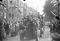 Photo from the NIOD's Huizinga collection. A frantic crowd greets the entering vehicles of the Princess Irene brigade in The Hague early in the evening on May 8, 1945.