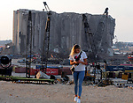 Lebanese woman stand at Beirut port, is seen near the damaged grain silo, in Beirut, Lebanon December 22, 2020. Photo by Haitham Moussawi