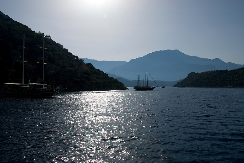 Sunset on the Turquoise Coast of Turkey.  Broad-beamed wooden coastal sailing vessels were first used to transport cargo on ancient Mediterranean trade routes. Today Turkish gulet vessels are beautiful floating villas for tourists and vacationing locals, mostly motoring along the shoreline.