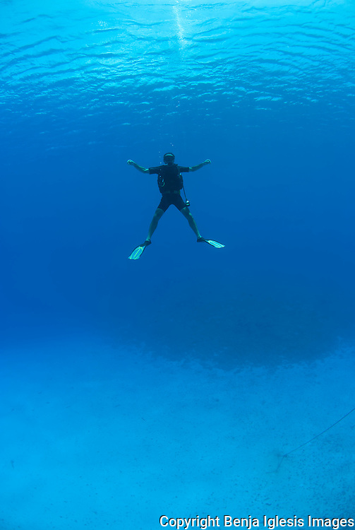 Diver floating in the middle of Molokini Crater Maui Hawaii.
