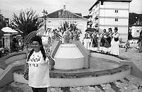 Festival di trombe e ottoni di Guca (Cacak). Una donna con indosso una maglietta con la scritta CCCP posa per una foto davanti a una fontana, sopra la quale suona una banda di donne in abito tradizionale --- Trumpet festival of Guca (Cacak). A woman wearing a CCCP shirt poses for a photo in front of a fountain, over which a band of women wearing traditional clothes is playing