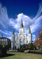 The exterior of an ornate building with a sweeping cloud mass in the background that looks like an angel. French Quarter, New Orleans, Louisiana.