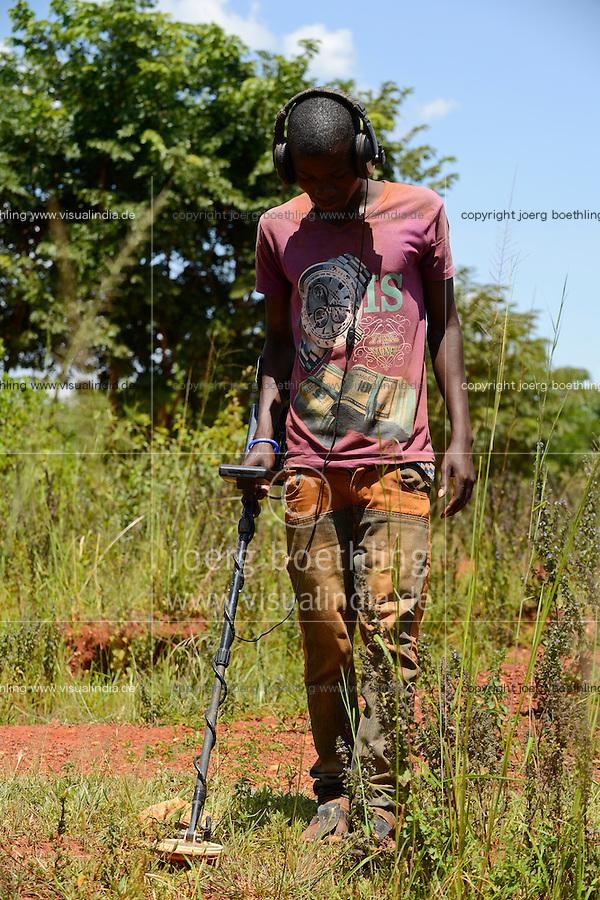 TANZANIA Geita, artisanal gold mining in Nyarugusu, man searching with metal detector for gold / TANSANIA Geita, kleine Goldminen in Nyarugusu, Mann sucht mit Detektor nach Gold