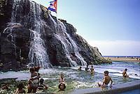 children play in a public fountain in Havana Cuba