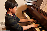 7 year old boy playing the piano during private instrumental lessons at public elementary school with music enrichment through public-private partnership