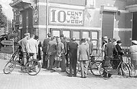 Photo from the NIOD's Huizinga collection. A group of people read a series of written wall papers on Conradkade. Overhead advertising for a newspaper: the News Source. 10 cents a week.
