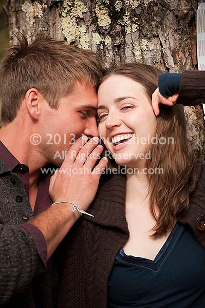 Young man wispering in woman's ear
