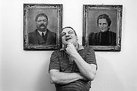 "Switzerland. Canton Ticino. Lugano. Giuliano Bignasca (born 10 avril 1945 - dead 7 march 2013). Founder and President for Life of "" Lega dei Ticinesi"".  Giuliano Bignasca stands in his office in front of the portraits of his grandparents. © 1995 Didier Ruef"