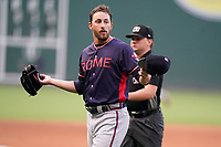 Starting pitcher A.J. Puckett (20) of the Rome Braves offers his hat, glove and belt for inspection of sticky substances by umpires Dylan Bradley and Joe Belangia in a game against the Greenville Drive on Tuesday, August 3, 2021, at Fluor Field at the West End in Greenville, South Carolina. (Tom Priddy/Four Seam Images)