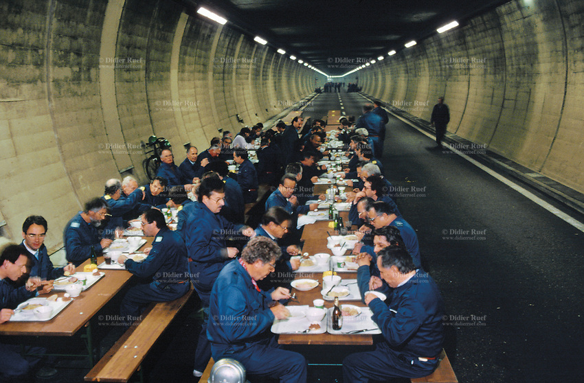 Switzerland. Canton Lucerne. Lunch time in the Sonnenberg tunnel in Lucerne during the largest civil defense exercise ever held in the country. From 16 to 21 November 1987, almost 1200 men and women converted a motorway tunnel into perhaps the world's largest bunker structure. The civil protectors had to prove during the exercise «Ameise» ( Ants in english) that in an emergency more than 20,000 inhabitants of the city of Lucerne could survive here in the mountain for two weeks. The Sonnenberg Tunnel is a 1,550m  long motorway tunnel, constructed between 1971 and 1976. At its completion it was also the world's largest civilian nuclear fallout shelter, designed to protect 20,000 civilians in the eventuality of war or disaster. Based on a federal law from 1963, Switzerland aims to provide nuclear fallout shelters for the entire population of the country. The construction of a new tunnel near an urban centre was seen as an opportunity to provide shelter space for a large number of people at the same time. The giant bunker was built between 1970 and 1976 at a cost of 40 million Swiss francs. The shelter consisted of the two motorway tunnels (one per direction of travel), each capable of holding 10,000 people in 64 person subdivisions. A seven story cavern between the tunnels contained shelter infrastructure including a command post, an emergency hospital, a radio studio, a telephone centre, prison cells and ventilation machines. The shelter was designed to withstand the blast from a 1 megaton nuclear explosion 1 kilometer away. The blast doors at the tunnel portals are 1.5 meters thick and weigh 350 tons. The logistical problems of maintaining a population of 20,000 in close confines were not thoroughly explored, and testing the installation was difficult because it required closing the motorway and rerouting the usual traffic. The only large-scale test, a five-day exercise in 1987 to practice converting the road tunnels into usable shelters, revealed many problems