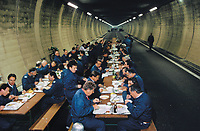 Switzerland. Canton Lucerne. Lunch time in the Sonnenberg tunnel in Lucerne during the largest civil defense exercise ever held in the country. From 16 to 21 November 1987, almost 1200 men and women converted a motorway tunnel into perhaps the world's largest bunker structure. The civil protectors had to prove during the exercise «Ameise » ( Ants in english) that in an emergency more than 20,000 inhabitants of the city of Lucerne could survive here in the mountain for two weeks. The Sonnenberg Tunnel is a 1,550 m  long motorway tunnel, constructed between 1971 and 1976. At its completion it was also the world's largest civilian nuclear fallout shelter, designed to protect 20,000 civilians in the eventuality of war or disaster. Based on a federal law from 1963, Switzerland aims to provide nuclear fallout shelters for the entire population of the country. The construction of a new tunnel near an urban centre was seen as an opportunity to provide shelter space for a large number of people at the same time. The giant bunker was built between 1970 and 1976 at a cost of 40 million Swiss francs. The shelter consisted of the two motorway tunnels (one per direction of travel), each capable of holding 10,000 people in 64 person subdivisions. A seven story cavern between the tunnels contained shelter infrastructure including a command post, an emergency hospital, a radio studio, a telephone centre, prison cells and ventilation machines. The shelter was designed to withstand the blast from a 1 megaton nuclear explosion 1 kilometer away. The blast doors at the tunnel portals are 1.5 meters thick and weigh 350 tons. The logistical problems of maintaining a population of 20,000 in close confines were not thoroughly explored, and testing the installation was difficult because it required closing the motorway and rerouting the usual traffic. The only large-scale test, a five-day exercise in 1987 to practice converting the road tunnels into usable shelters, revealed many problems
