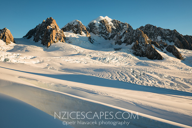 Sunset over second highest peak of Southern Alps, Mount Tasman 3497m in centre with Mt. Lendenfeld 3194m and Mount Haast 3114m on left and Torres Peak 3160m on right, Westland Tai Poutini National Park, West Coast, UNESCO World Heritage, New Zealand, NZ