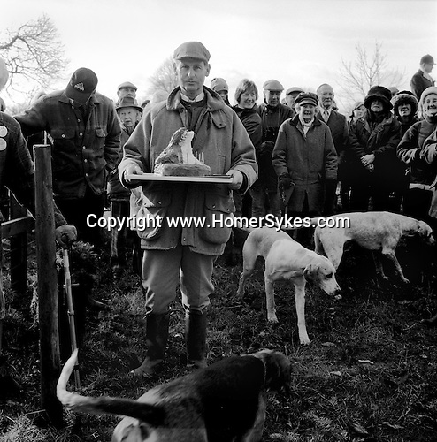 The Duke of Beauforts Hunt...The meet at the home of Mrs Elizabeth Pope to celebrate her 90th birthday. A chocolate cake in the form of a mounted foxs mask is presented, before being distributed amongst the well wishers. Near Avening, Gloucestershire.