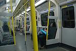 Woman asleep on tube train at night. London UK
