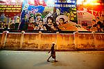 A man walks under a set of illuminated Communist propaganda posters in the Central Highlands town of Kon Tum, Vietnam. April 13, 2012.