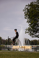"""A bicyclist atop a """"penny-farthing' or 'high wheel' bicycle passing the fountain in Denver's City Park."""
