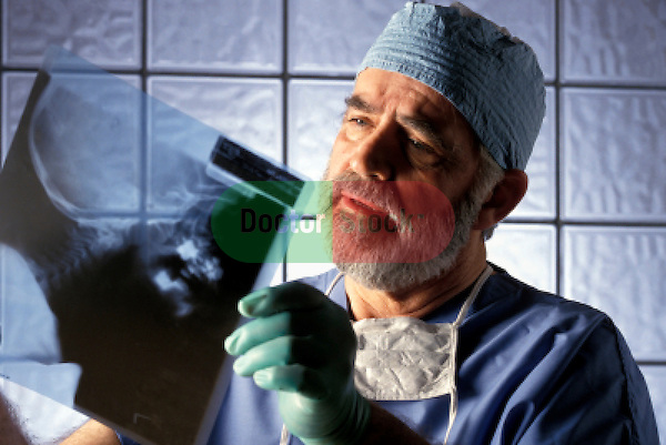surgeon in scrubs looking intensely at x-ray