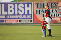 Trayce Thompson #24 of the Kannapolis Intimidators and a young fan during the National Anthem at Fieldcrest Cannon Stadium May 12, 2010, in Kannapolis, North Carolina.  Photo by Brian Westerholt / Four Seam Images